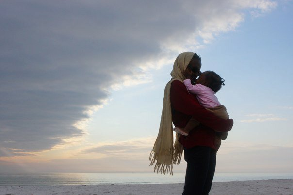 Black mother and baby daughter embracing seaside at sunset.