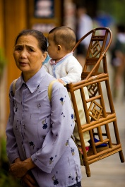 A Chinese grandmother uses a traditional strapped wooden baby carrier, chair.